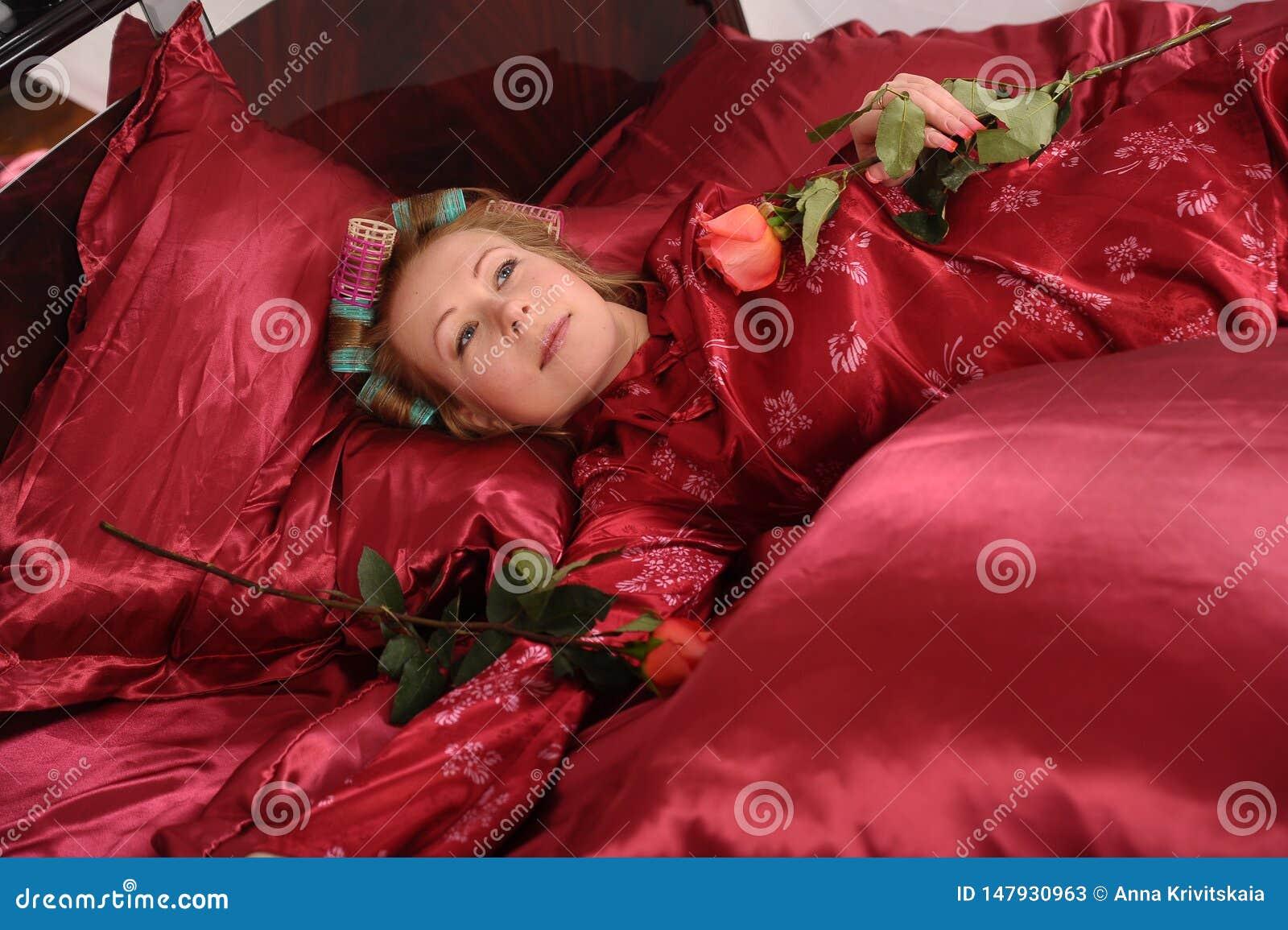 Mujer en los pijamas rojos que mienten en una cama en el lino rojo de seda con bigudíes de pelo y una rosa en su mano