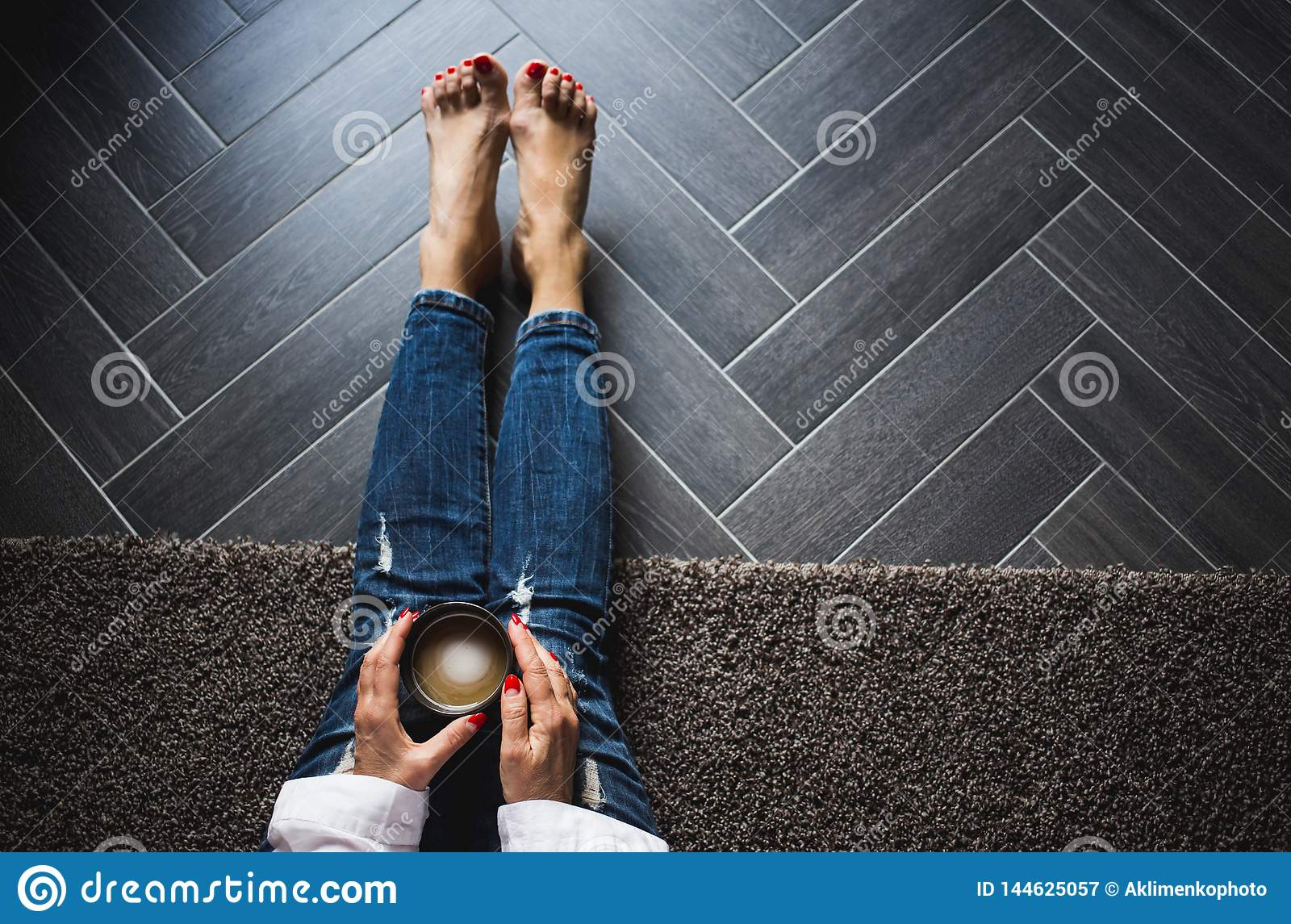 Mujer en los tejanos de moda que se sientan en el piso gris de madera, caf? driking Visi?n superior, cierre para arriba