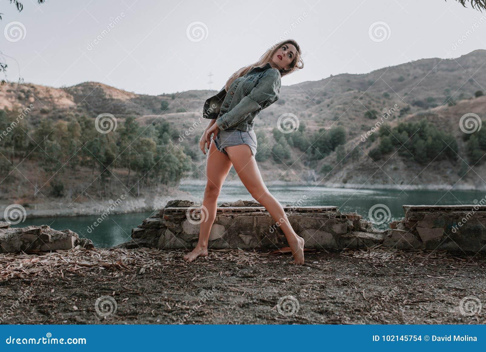 Mujer en pantalones cortos y chaqueta que presenta en naturaleza