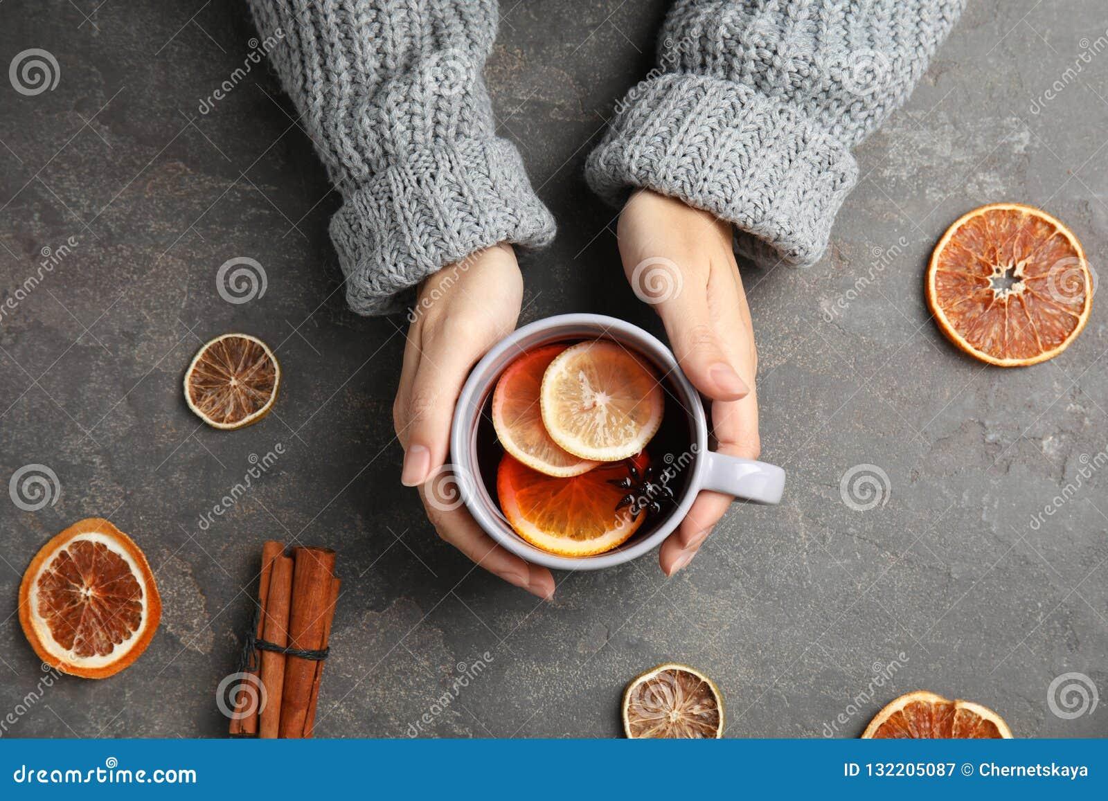 Mujer en suéter caliente con la taza
