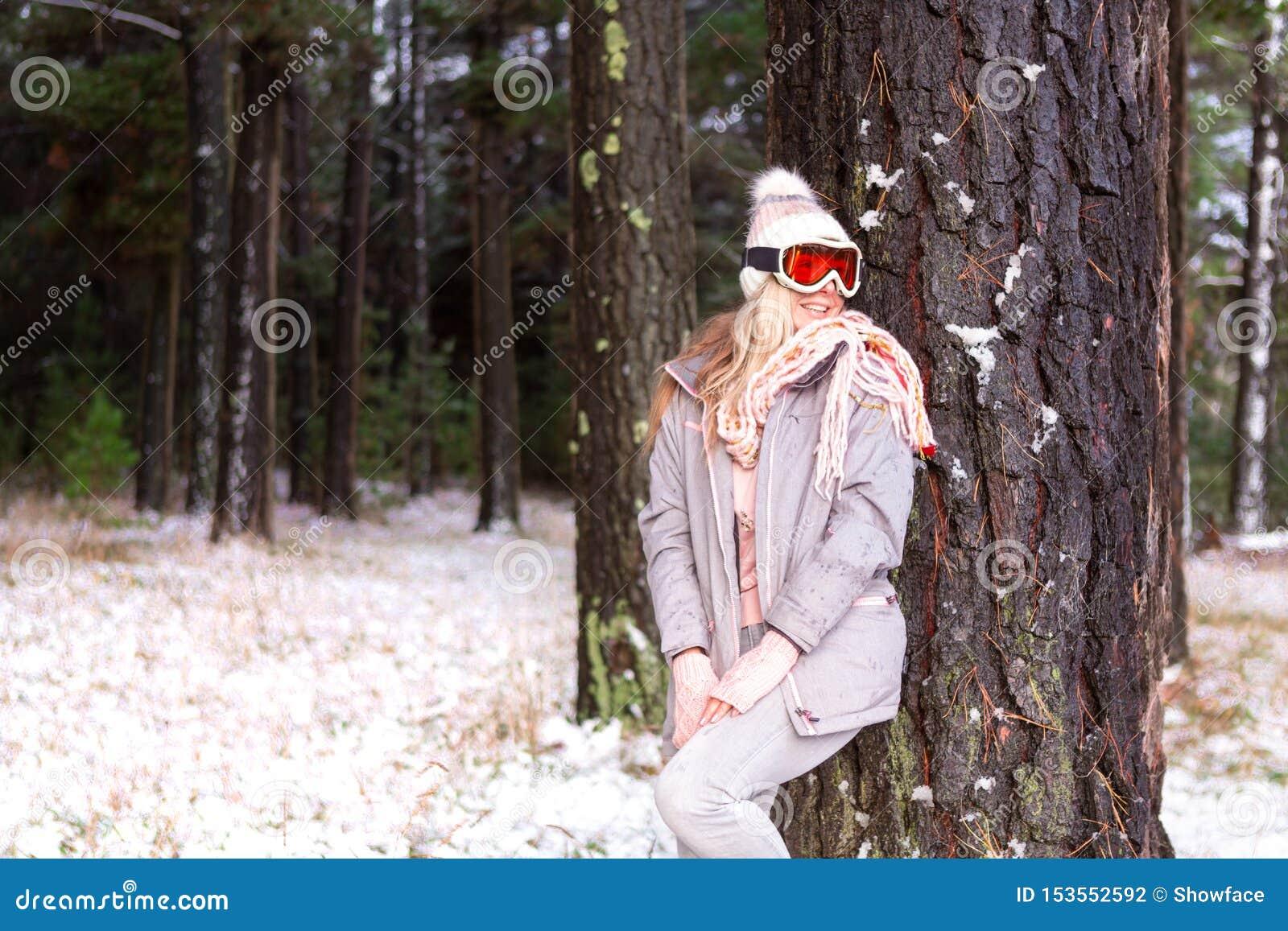 Mujer en un arbolado nevoso de los árboles de pino