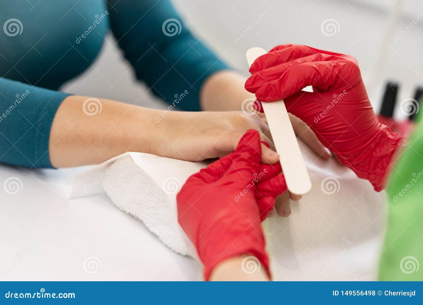Mujer en un sal?n del clavo que recibe una manicura de un cosmet?logo con el fichero de clavo
