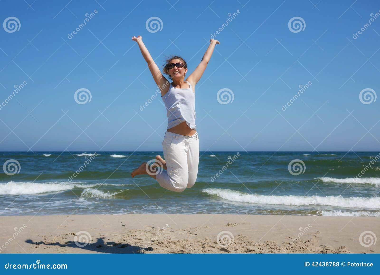 Mujer en un tiro en suspensión en la playa del mar Báltico