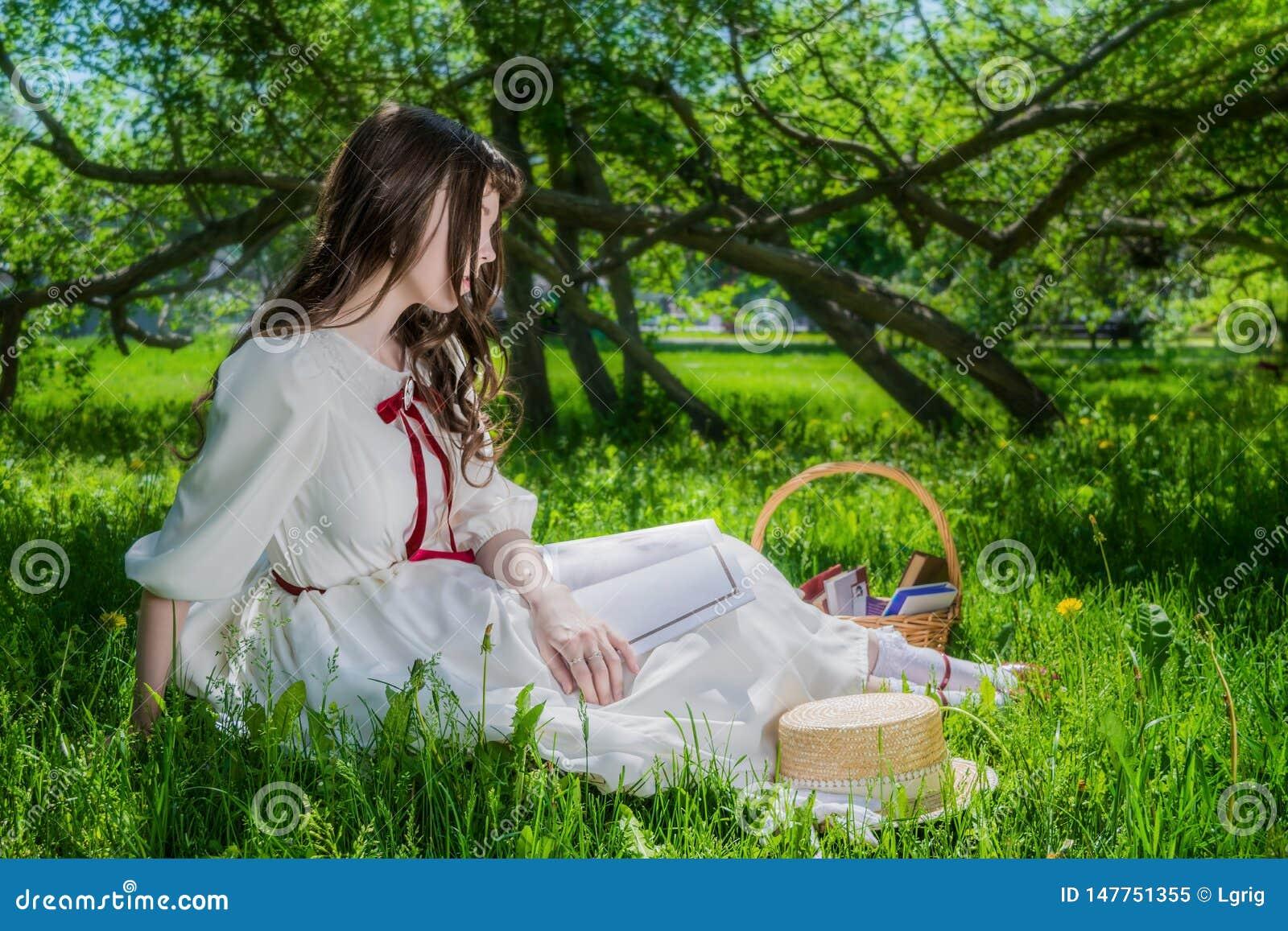 Mujer en un vestido blanco que se sienta debajo de lilas de un árbol