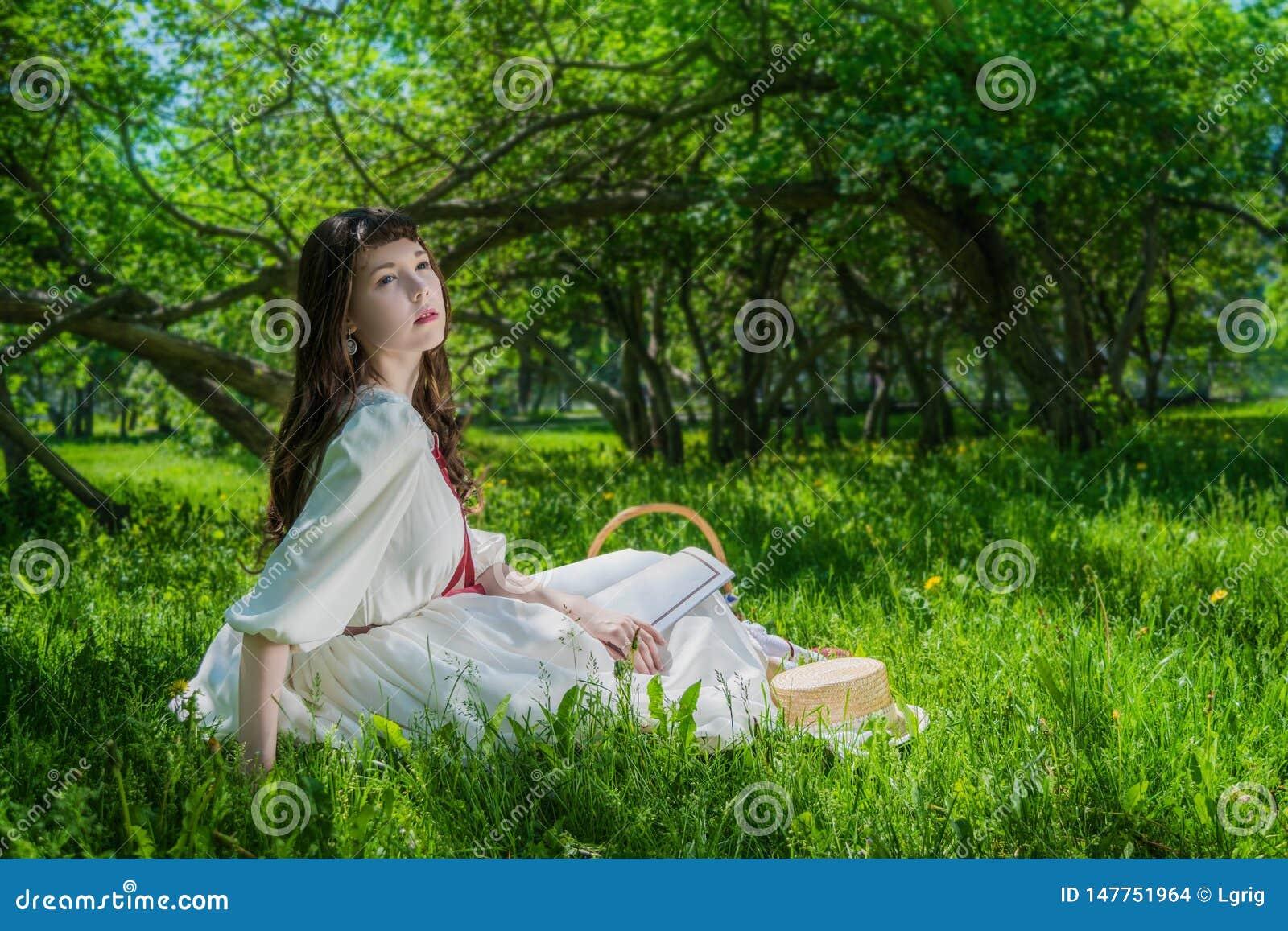 Mujer en un vestido blanco que se sienta debajo de lilas de un ?rbol