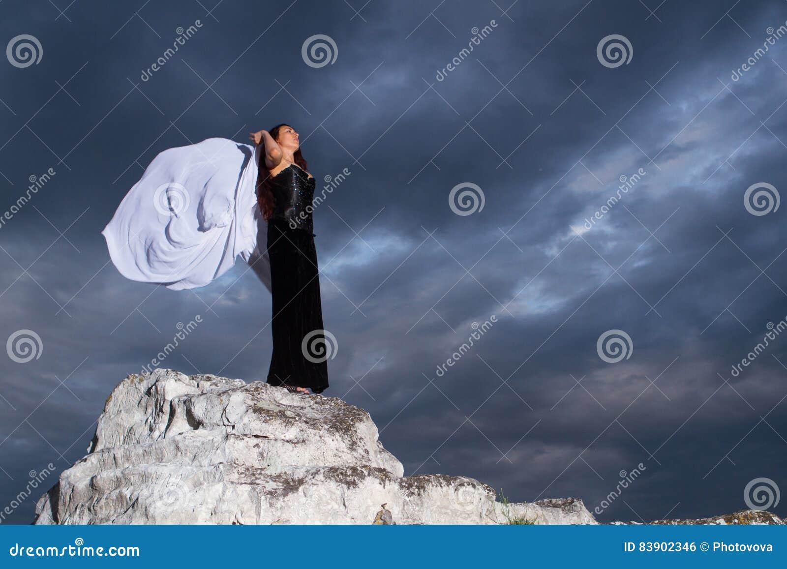 Mujer en un vestido negro en un fondo del cielo nublado