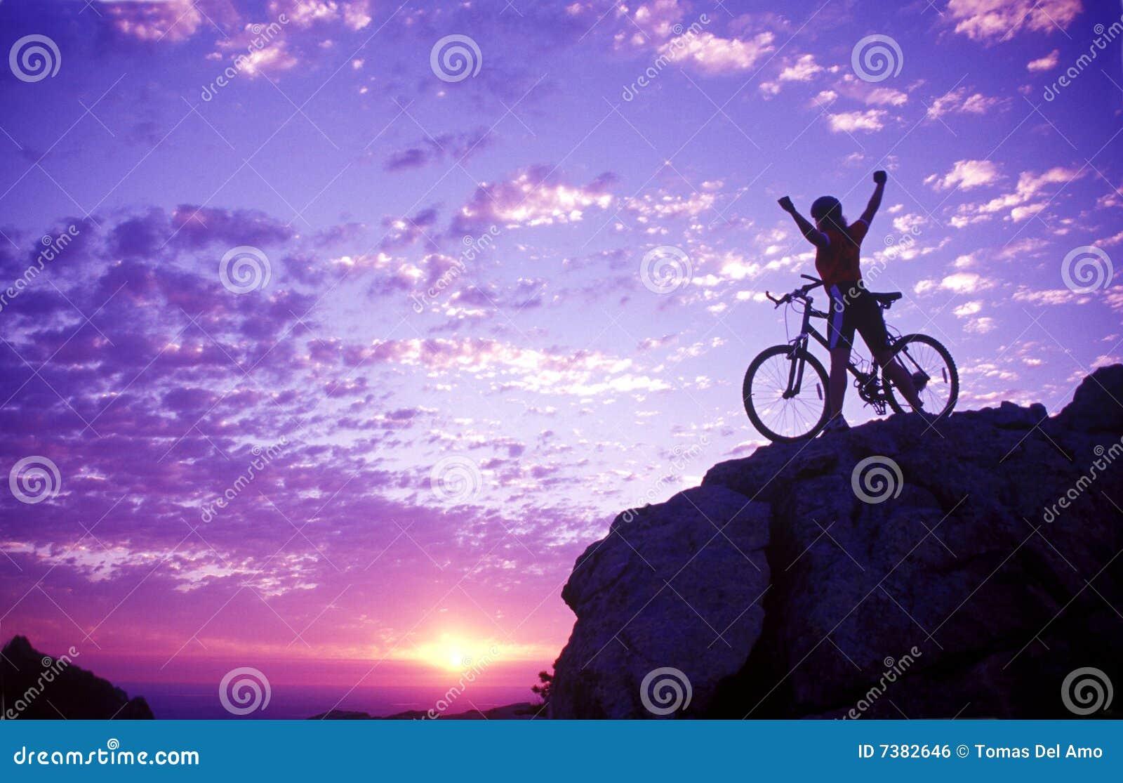 Mujer en una cima de la montaña con la bici