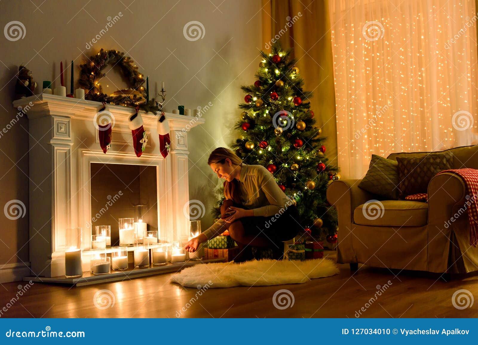 Mujer en velas de fijación encendidas de un cuarto de la Navidad
