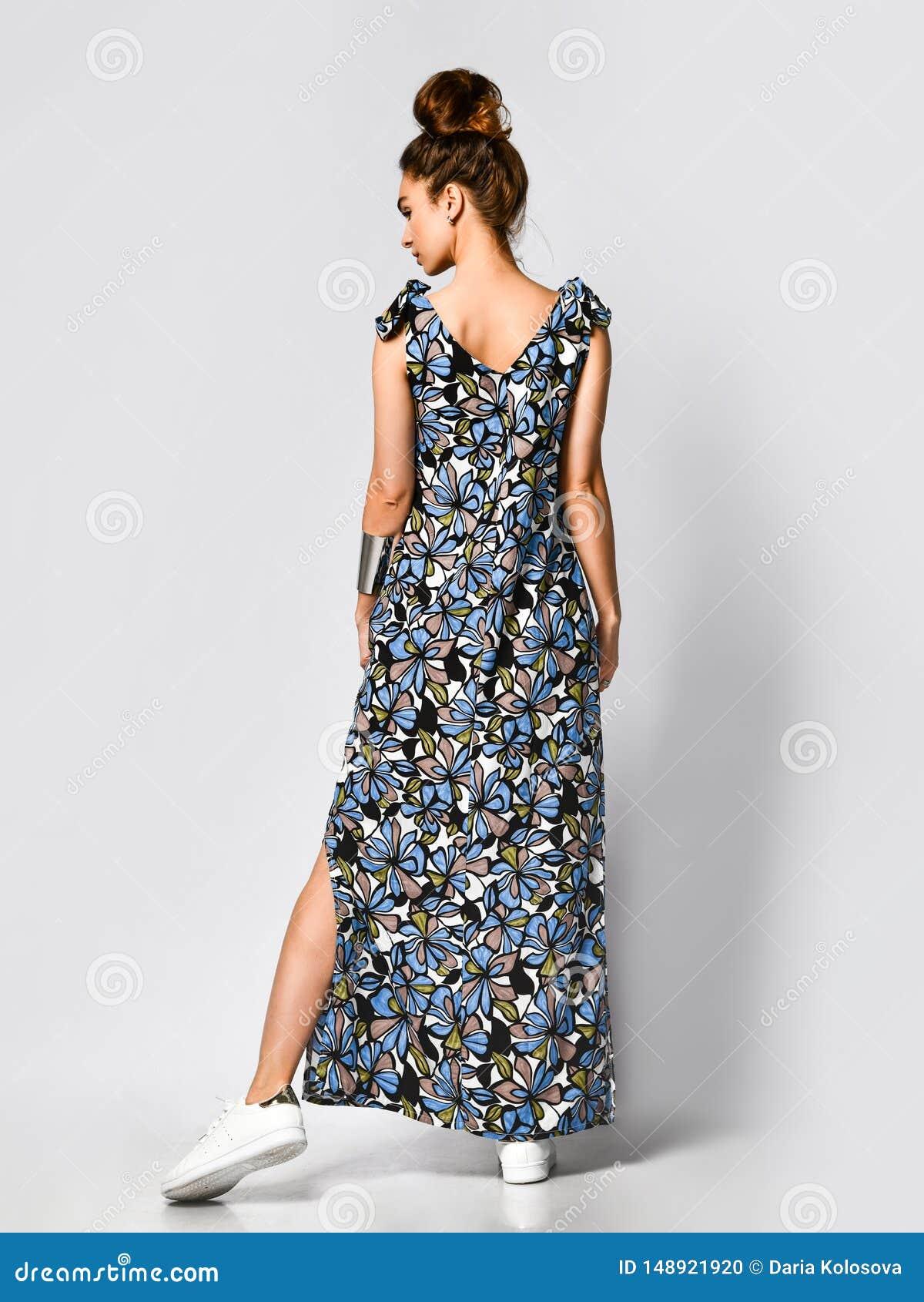 Mujer en vestido de flores largo en la tienda de la moda - retrato de la muchacha en una tienda de ropa en un vestido maxi del ve