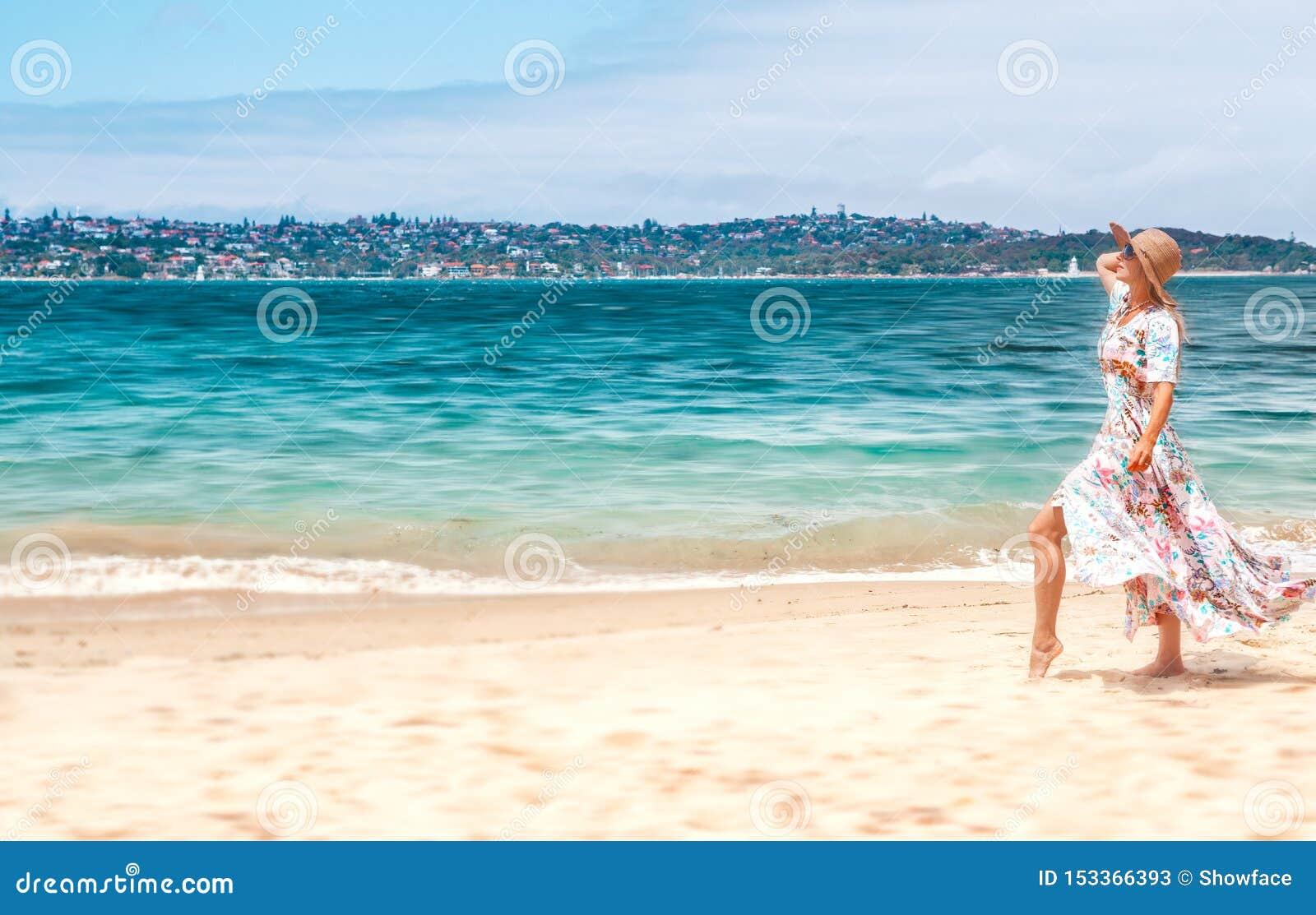 Mujer en vestido que fluye en la playa en Sydney Australia