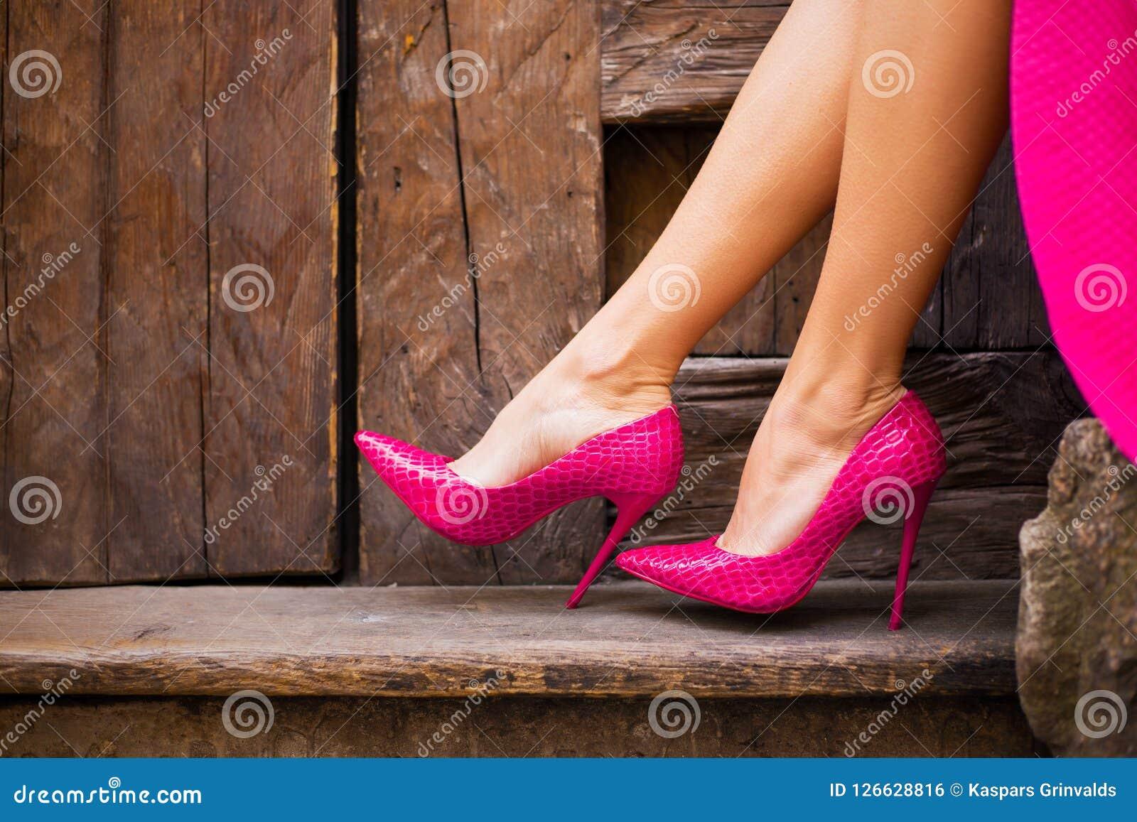 Mujer en zapatos rosados del tacón alto