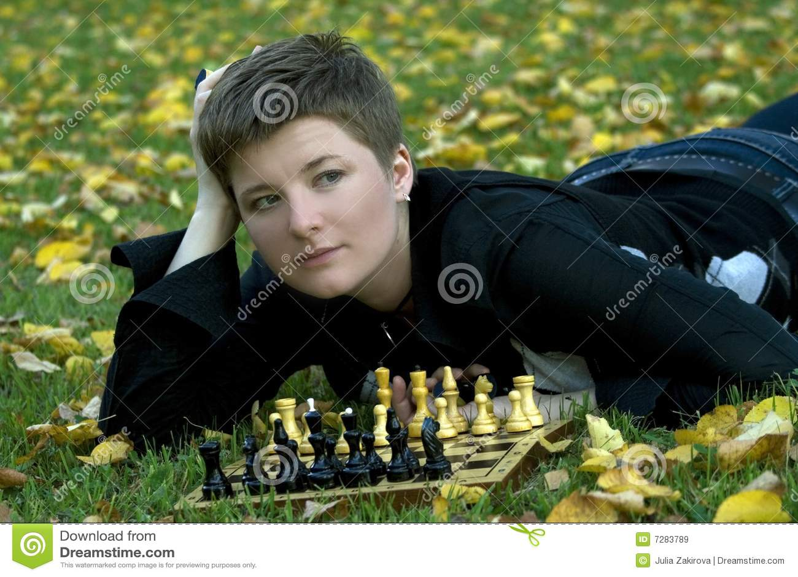 Mujer encantadora con la tarjeta de ajedrez