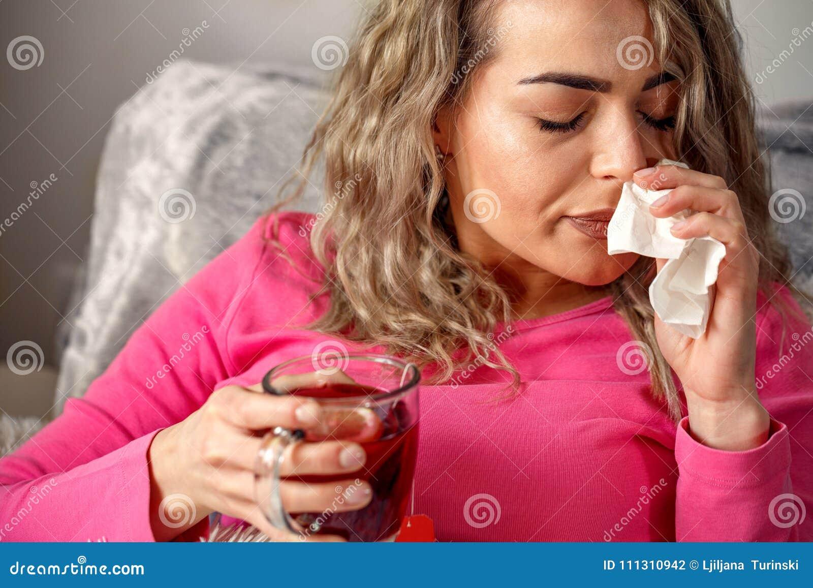 Mujer enferma que miente en cama con alta fiebre Ella es nariz que sopla