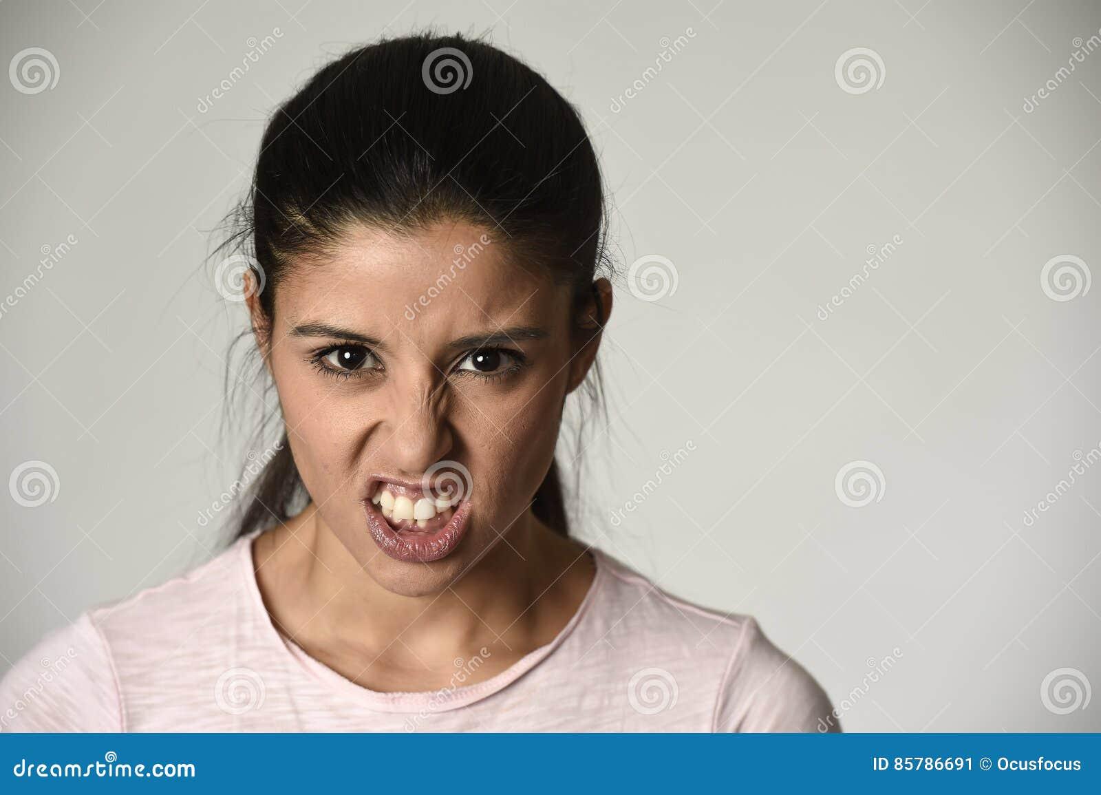 Mujer enojada y trastornada latina que parece cambiante furioso y loco en la emoción intensa de la cólera