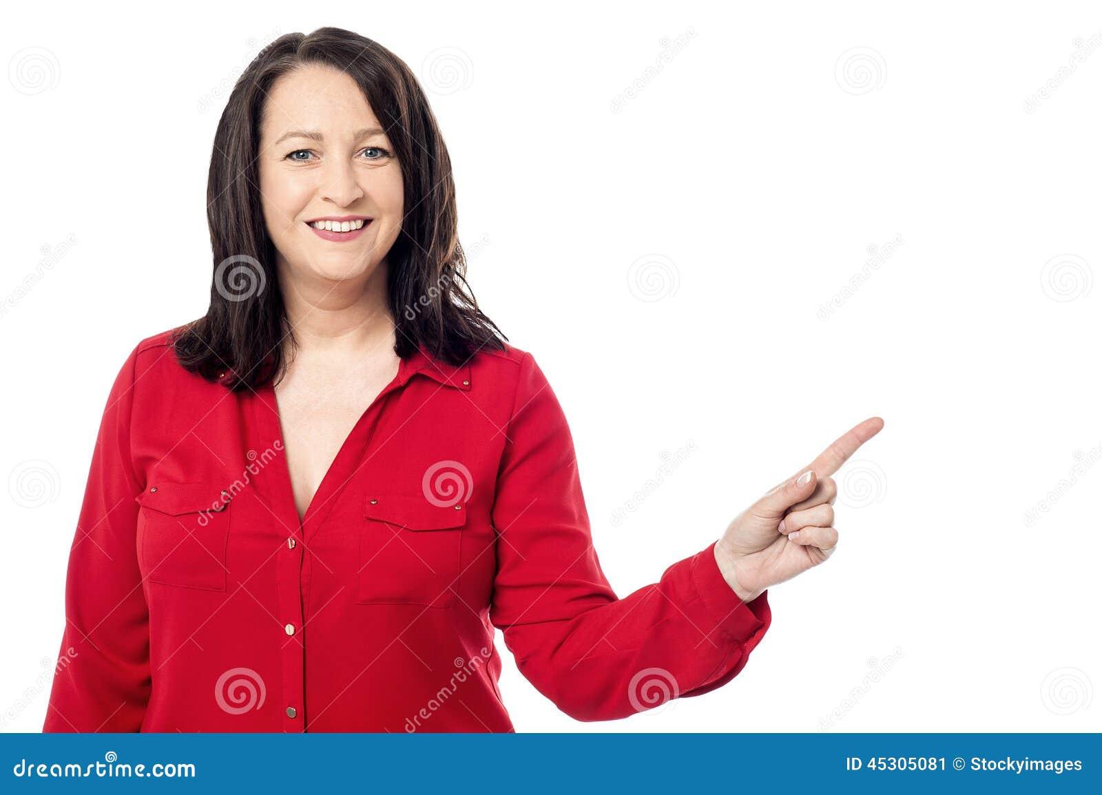 Mujer envejecida alegre que señala a su izquierda