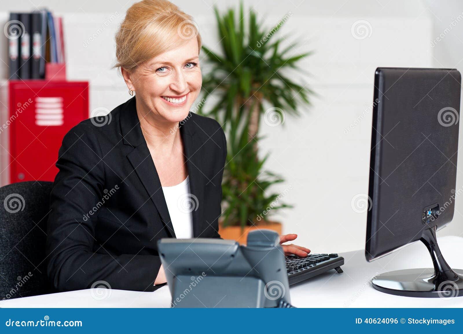 Mujer envejecida alegre que trabaja en el escritorio