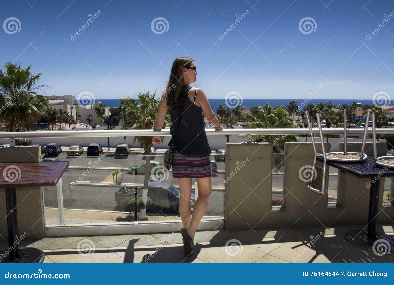 Mujer envejecida centro hermoso que mira el océano azul del balcón con el cielo azul profundo Pelo largo de Brown, top del tirant