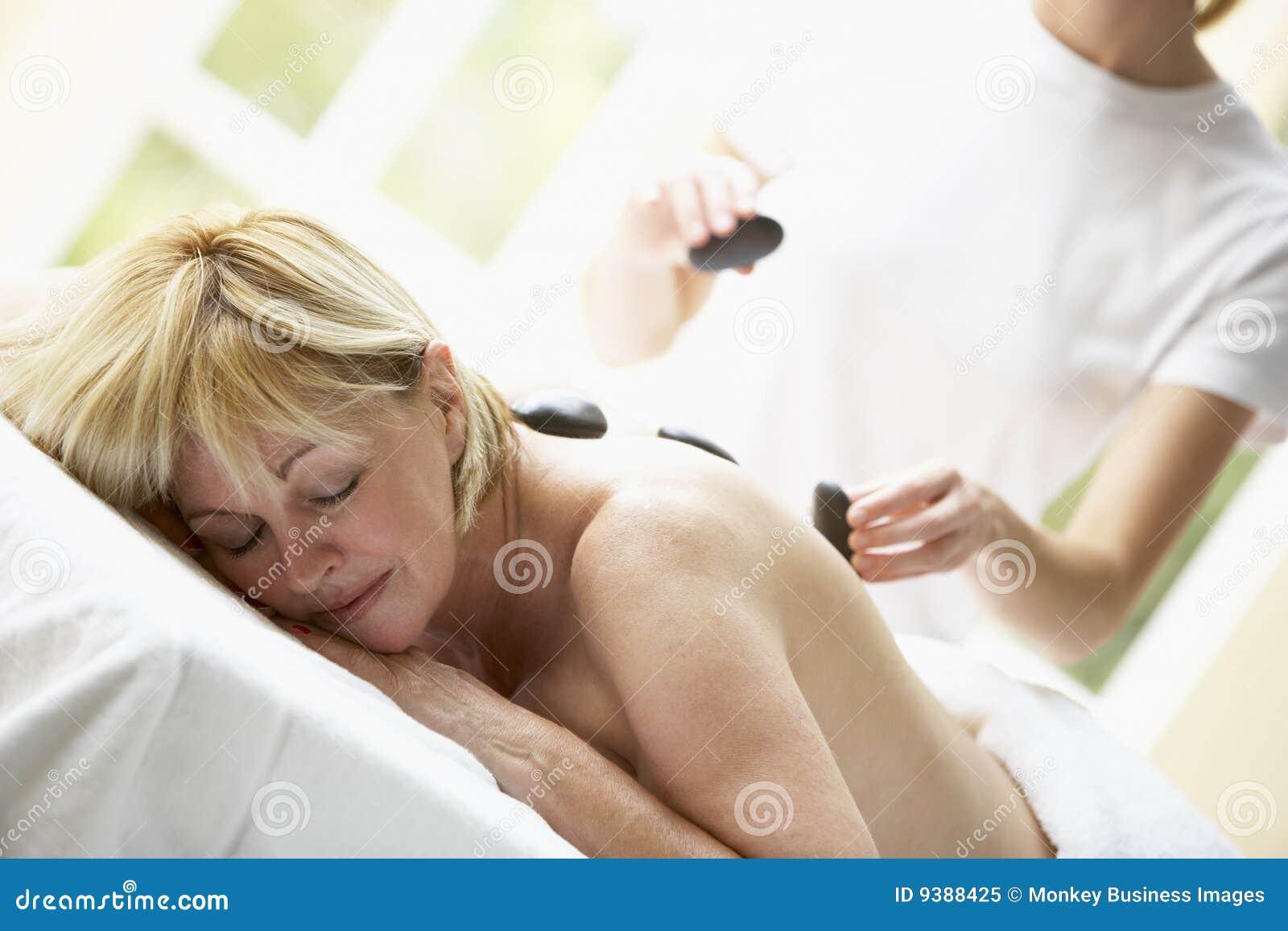 Mujer envejecida media que disfruta del tratamiento de piedra caliente