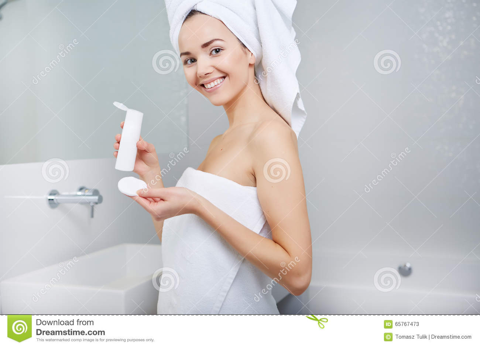 Mujer Envuelta Con Las Toallas De Baño, Aplicando La Crema En Su Cara Foto de