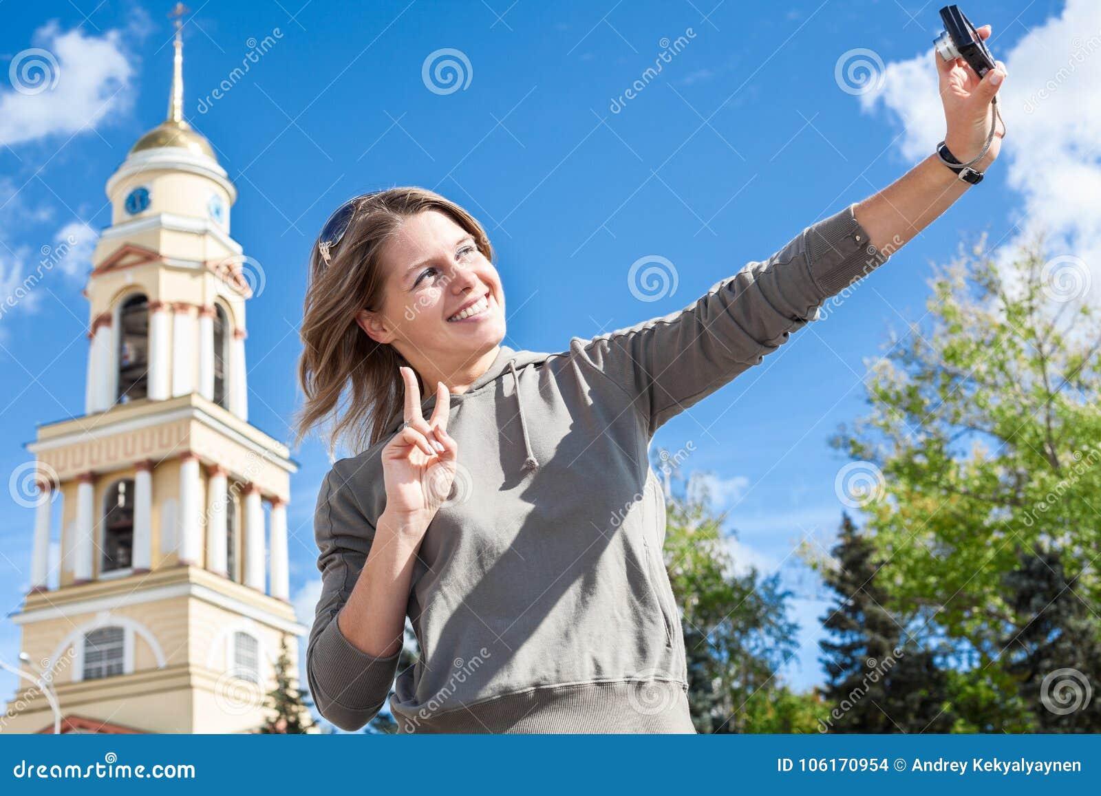 Mujer europea sonriente de los jóvenes que toma la imagen del autorretrato con la cámara fácilmente manejada contra el campanario