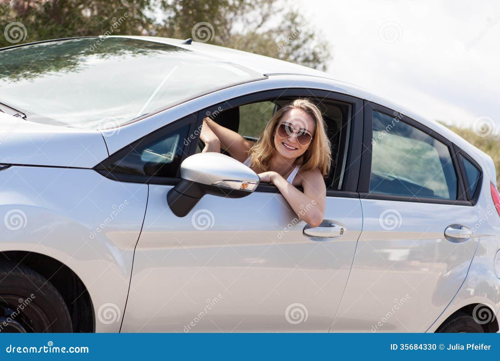 Mujer feliz atractiva joven que se sienta en verano del coche