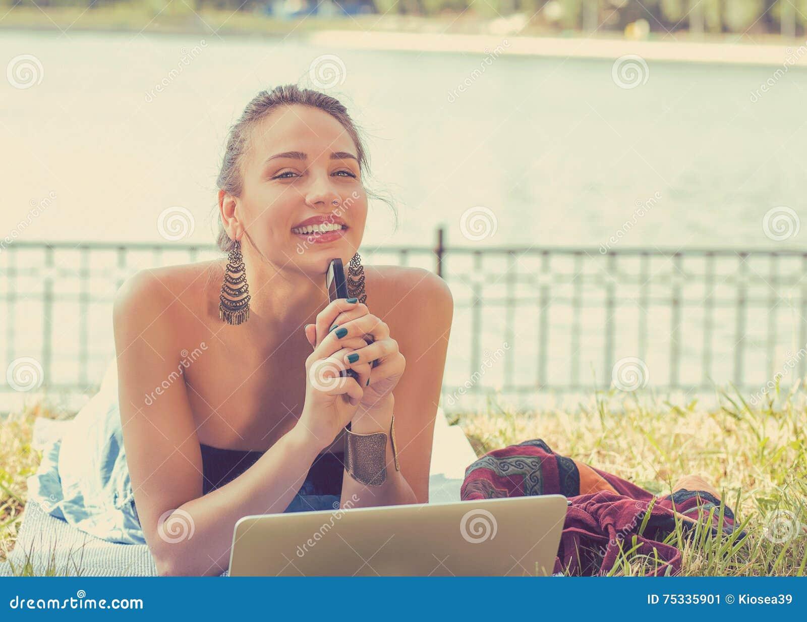 Mujer feliz con el ordenador portátil y el teléfono móvil que se relajan en un parque