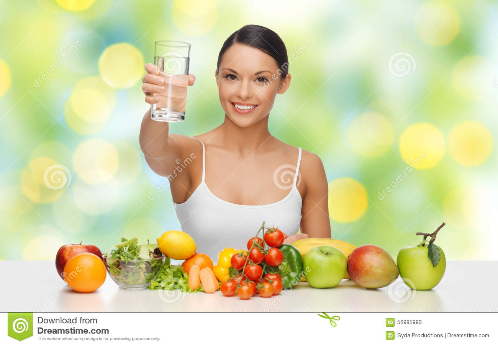 Mujer feliz con la comida sana que muestra el vidrio de agua