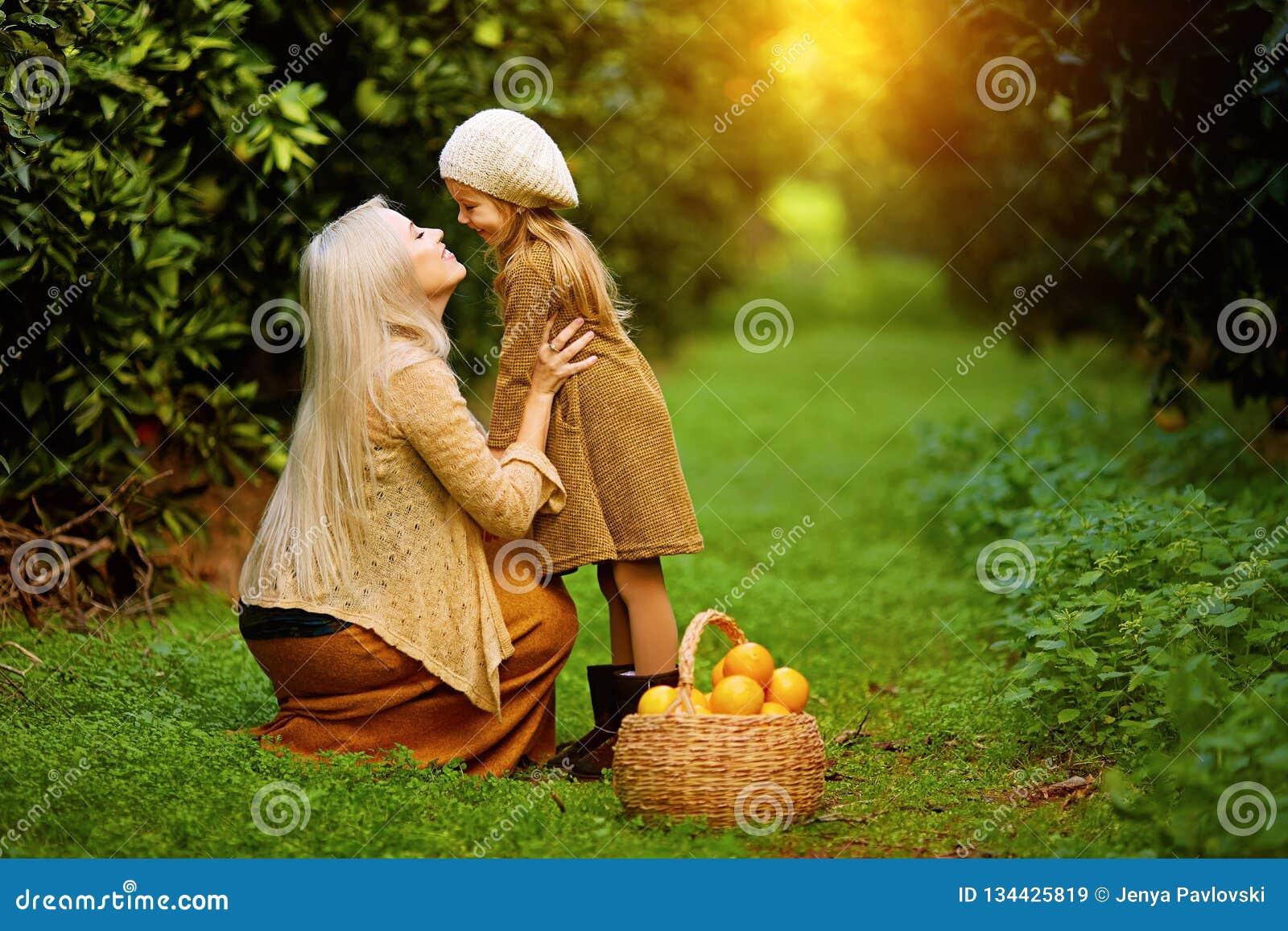 Mujer feliz con la hija en jardín soleado