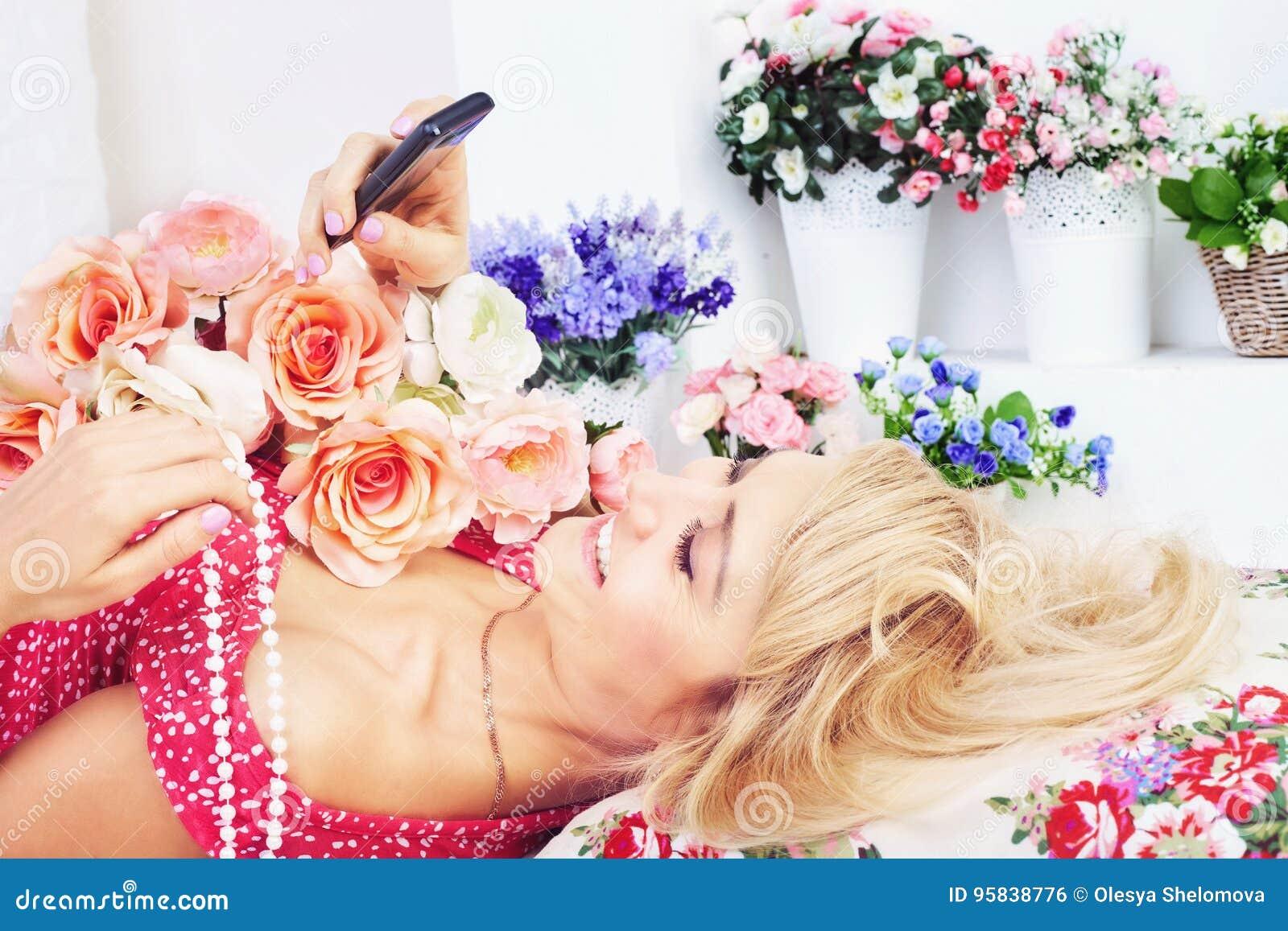 Mujer feliz con las flores que mandan un SMS al mensaje en el teléfono