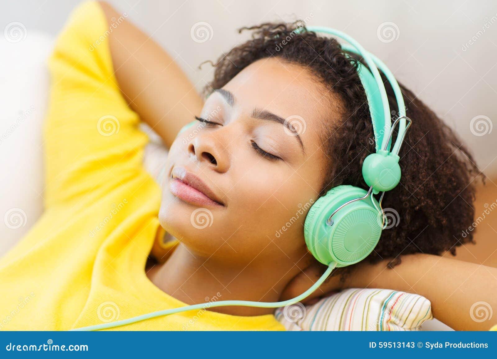 Mujer feliz con los auriculares que escucha la música
