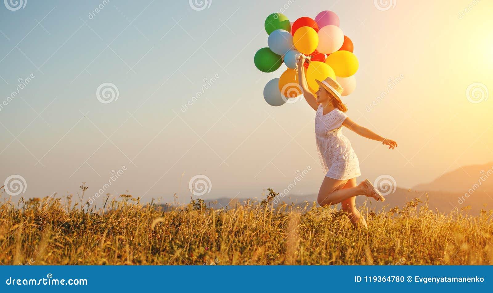 Mujer feliz con los globos en la puesta del sol en verano