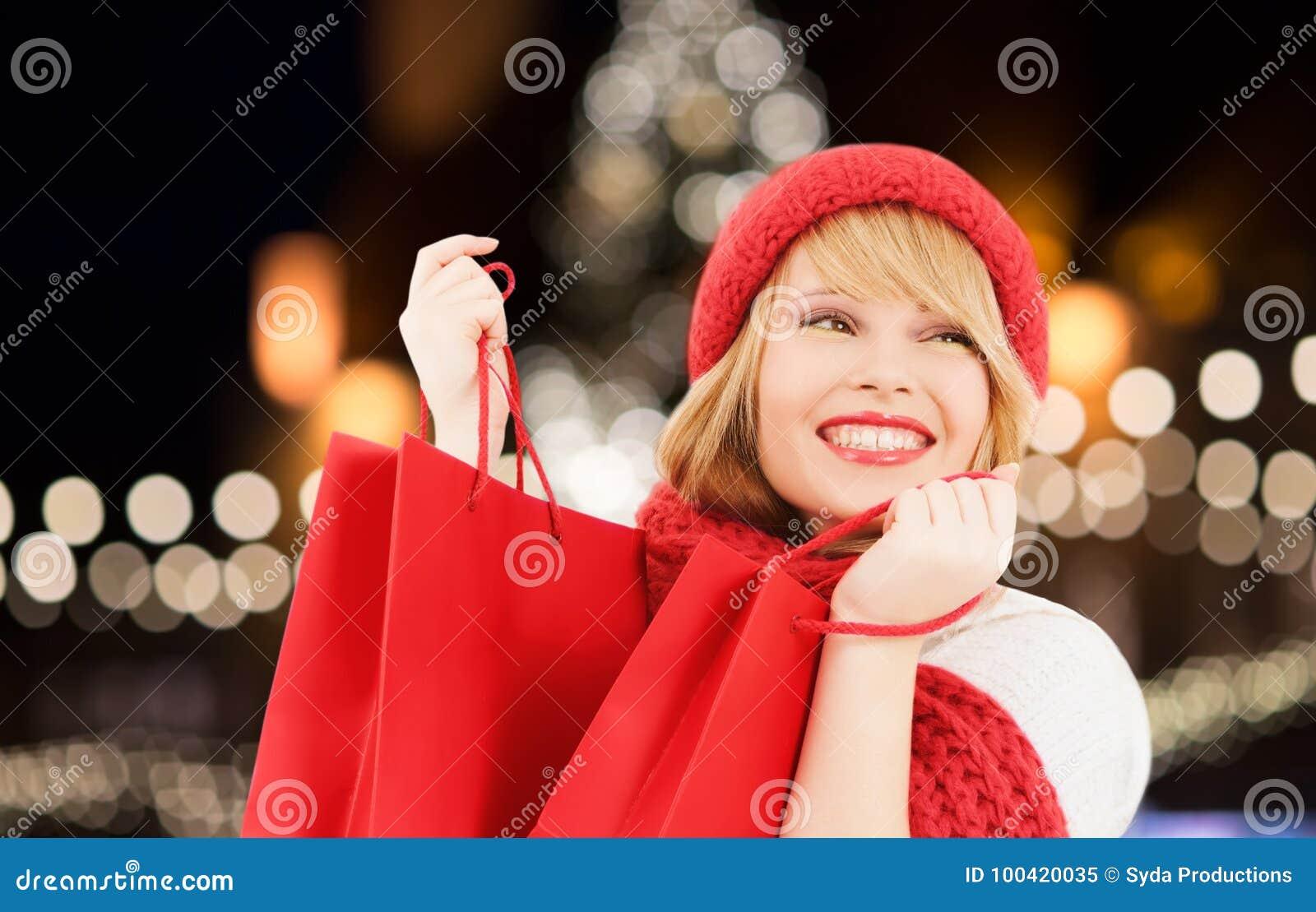 Mujer feliz con los panieres sobre el árbol de navidad