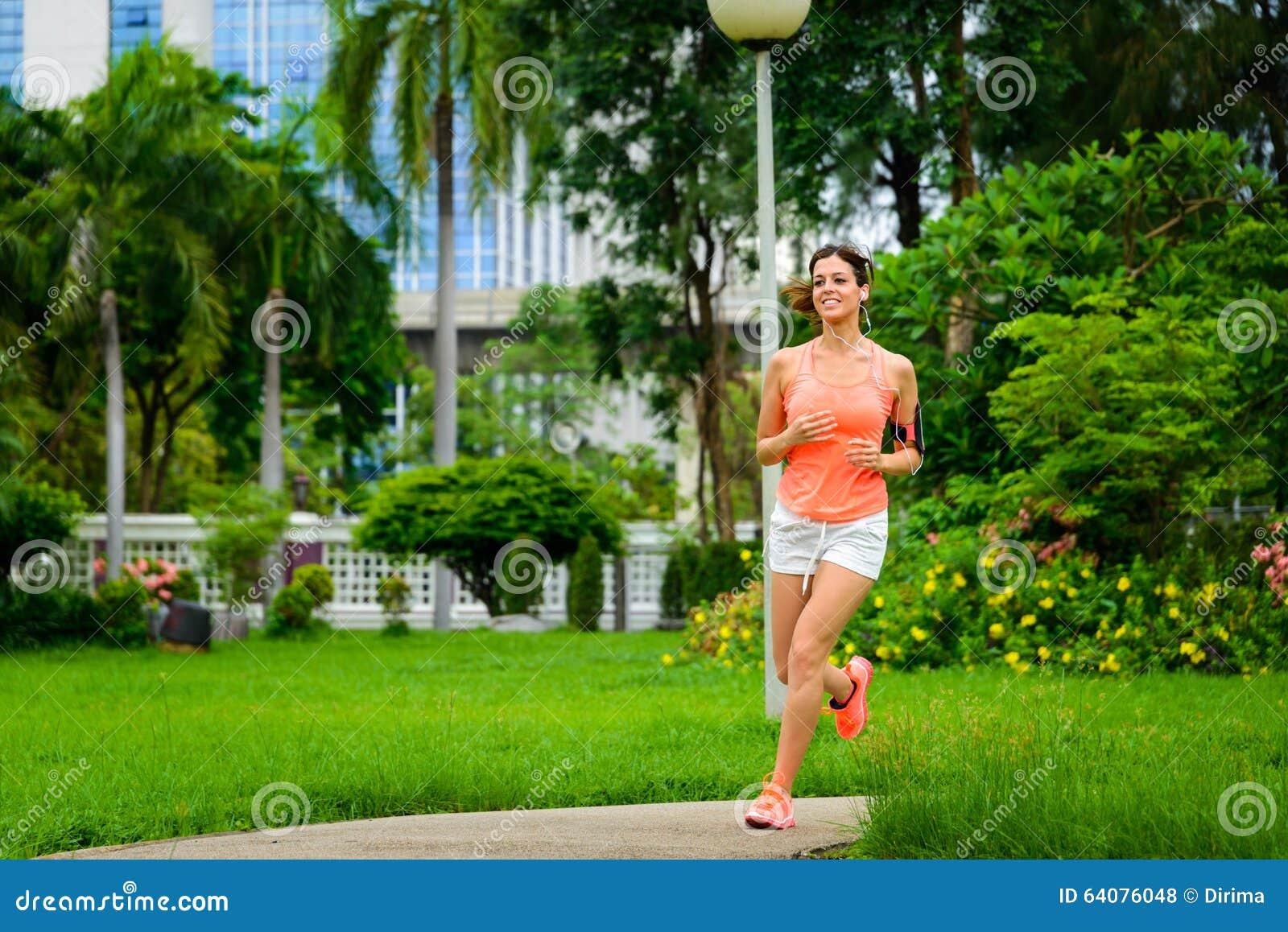 Mujer feliz de la aptitud que corre en el parque de la ciudad