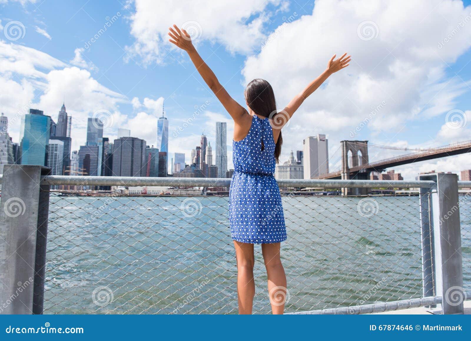 Mujer feliz de la libertad que anima en el horizonte urbano de NYC New York City