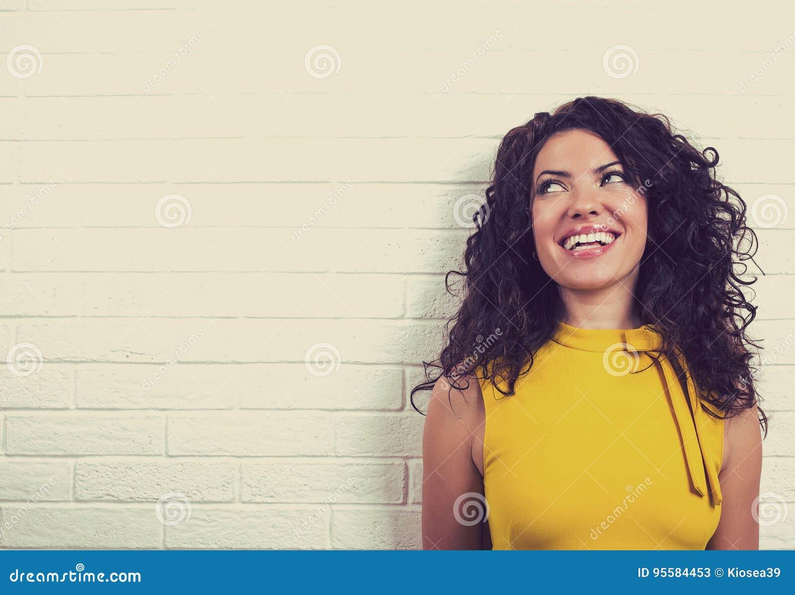 Mujer feliz de risa, aislada en fondo de la pared de ladrillo