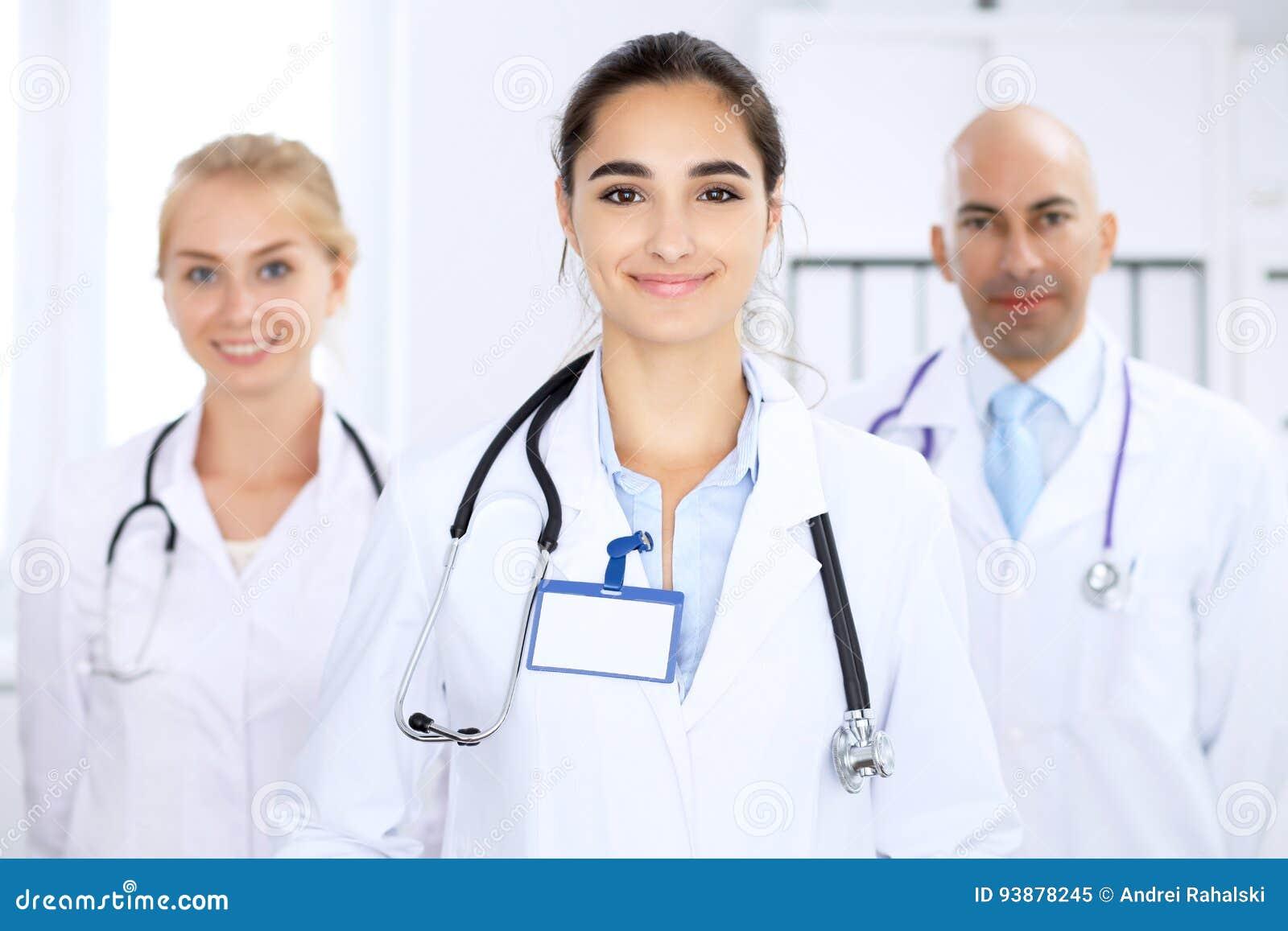Mujer feliz del doctor con el personal médico en el hospital