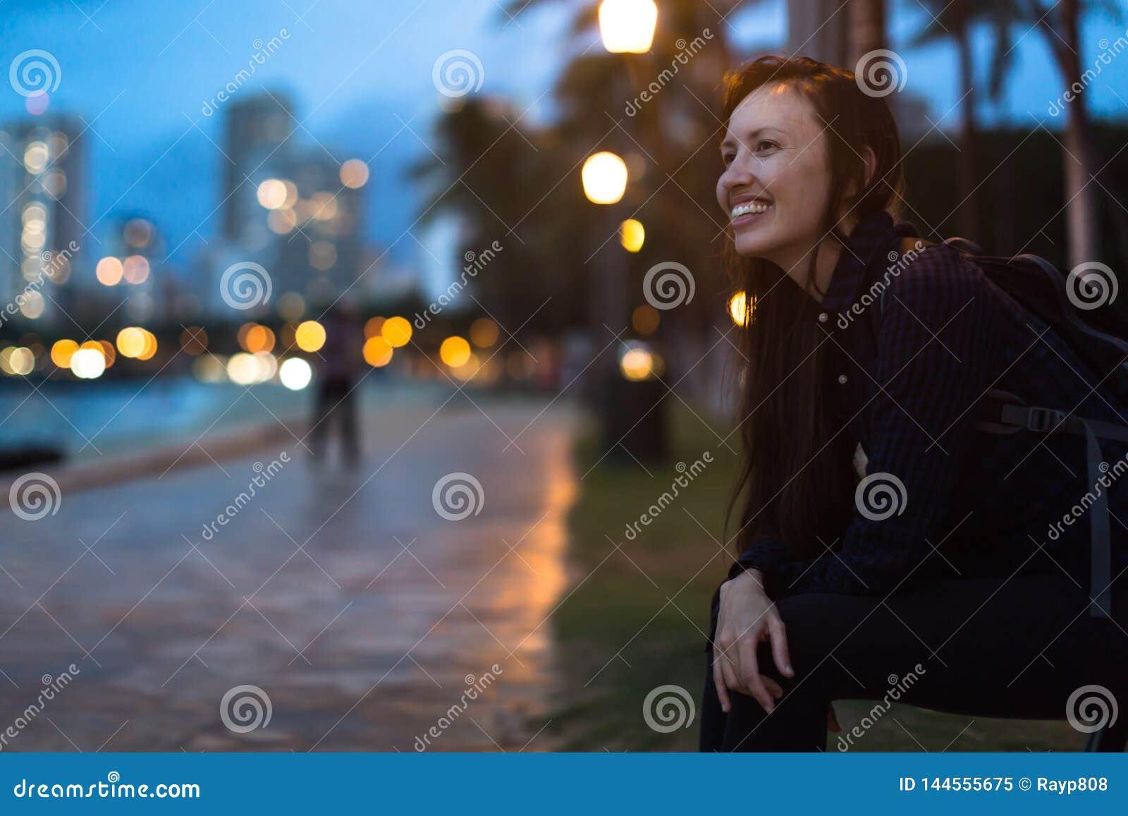 Mujer feliz del estudiante universitario que goza del parque de la ciudad