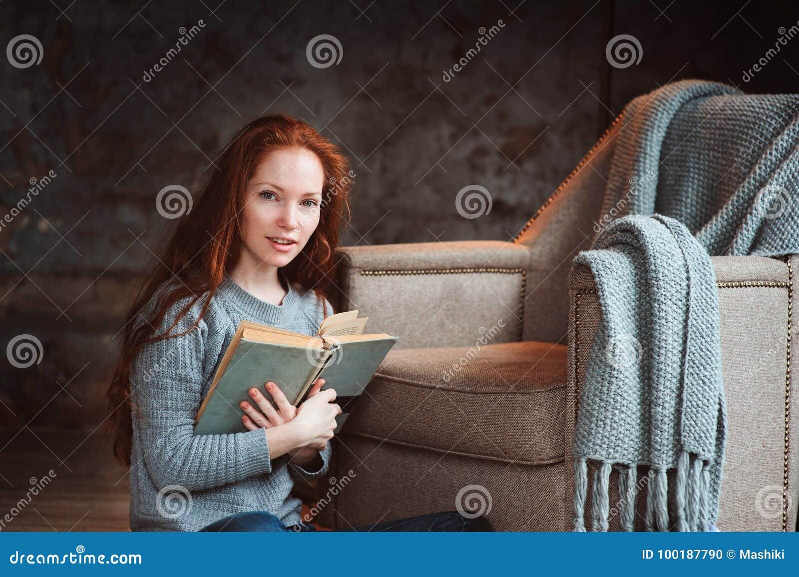 Mujer feliz del pelirrojo que se relaja en casa en fin de semana acogedor del invierno o del otoño con el libro y la taza de té c