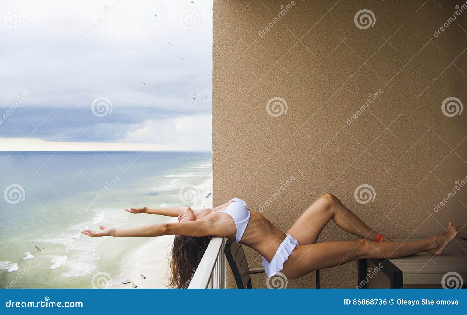 Mujer feliz en el bikini que estira en balcón en el mar