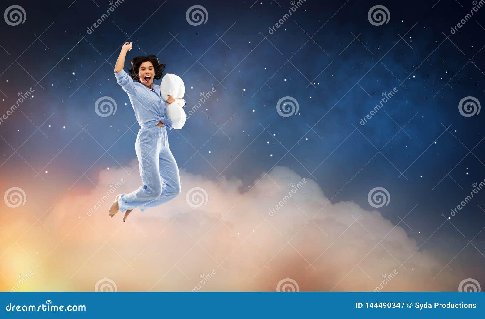 Mujer feliz en el pijama azul que salta con la almohada