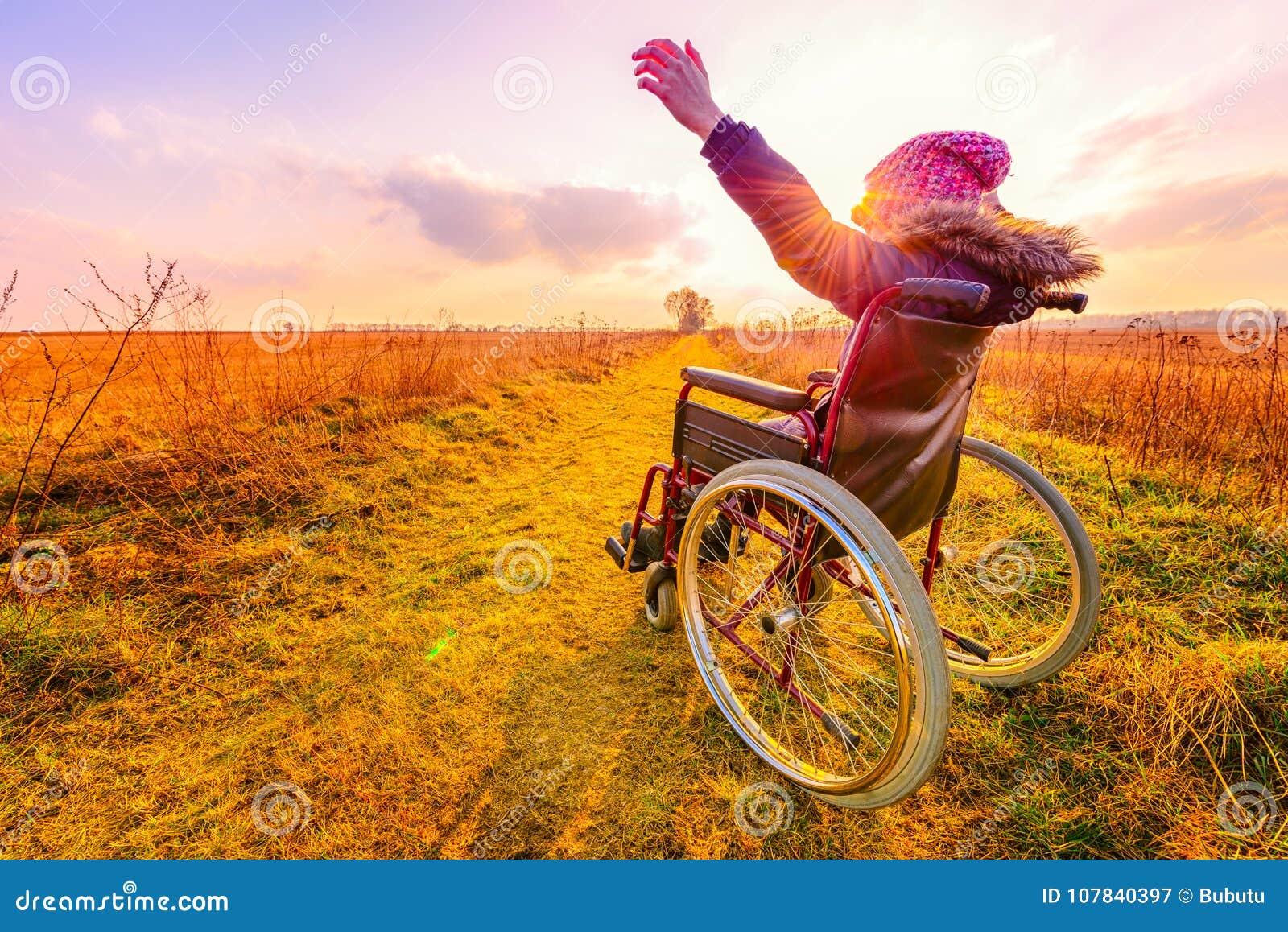 Mujer feliz en la puesta del sol Una chica joven en una silla de ruedas