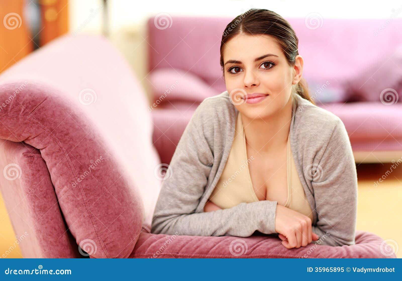 Mujer feliz hermosa que miente en el sofá en casa