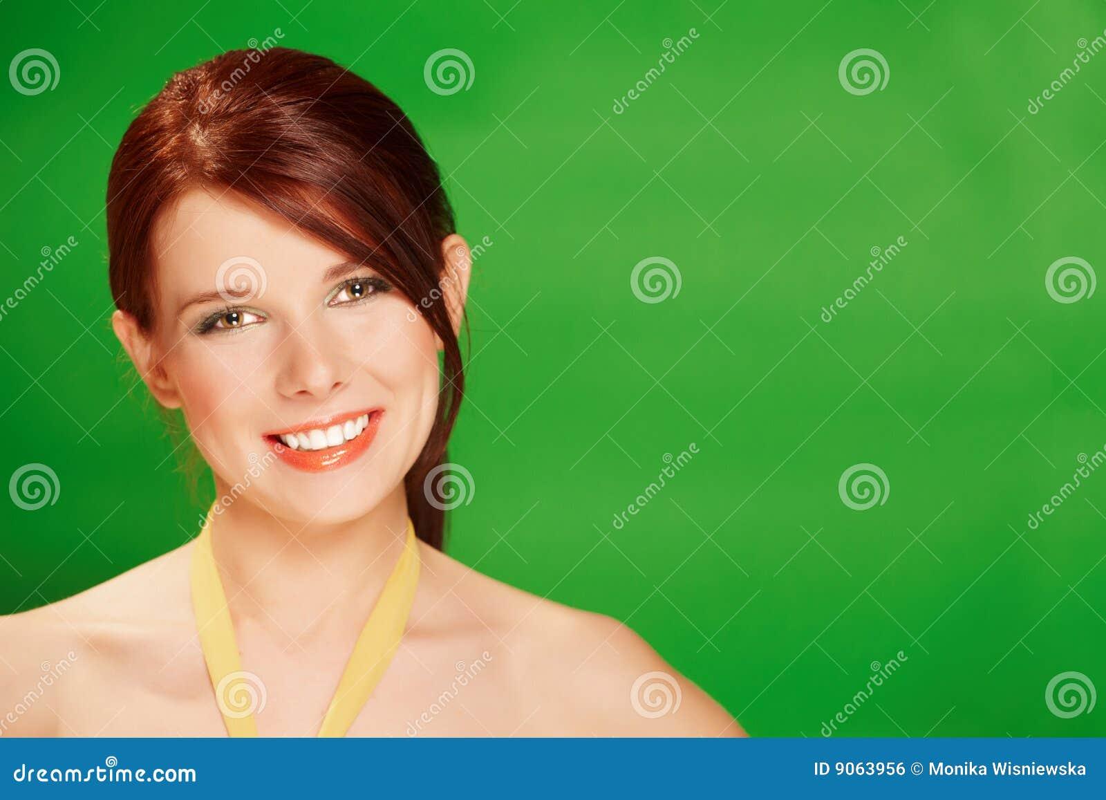 Mujer feliz joven hermosa en fondo verde