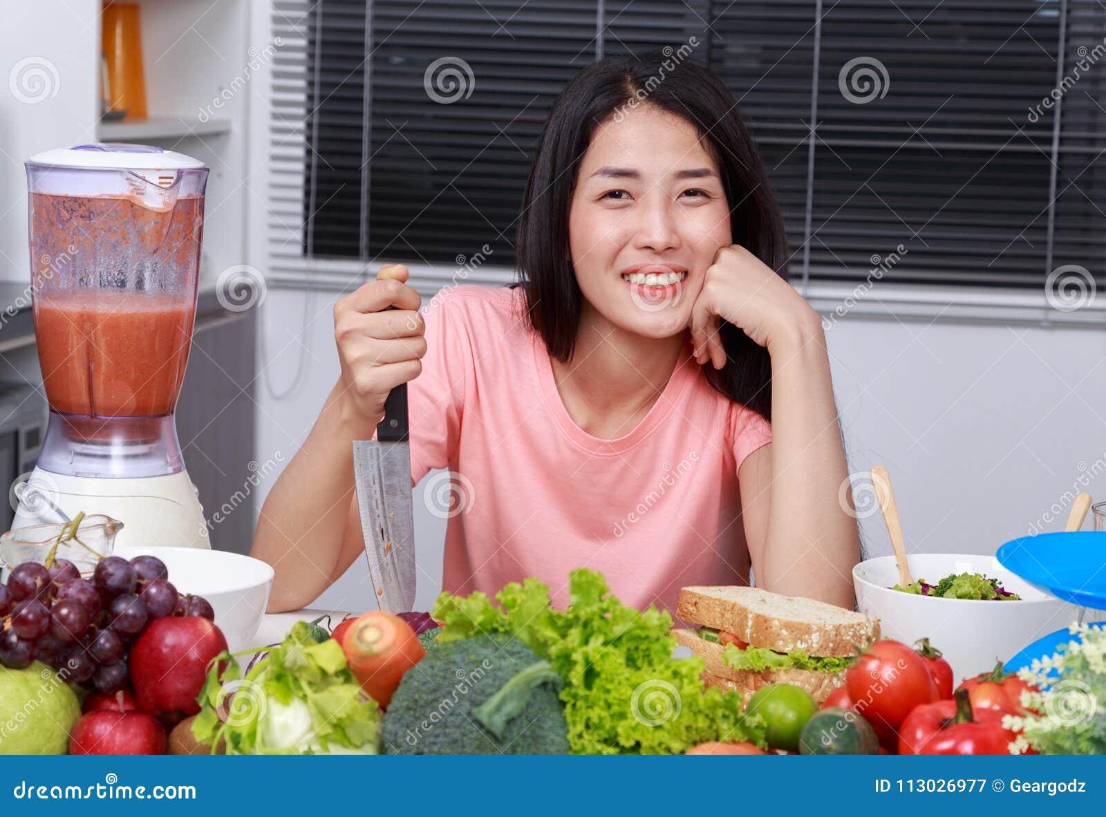 Mujer feliz que cocina con el cuchillo en sitio de la cocina
