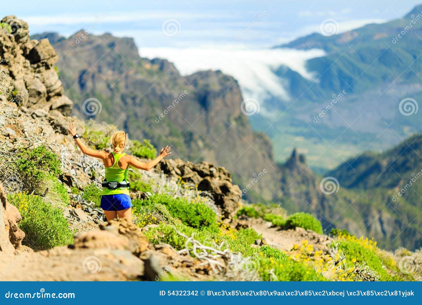 Mujer feliz que corre en montañas del verano