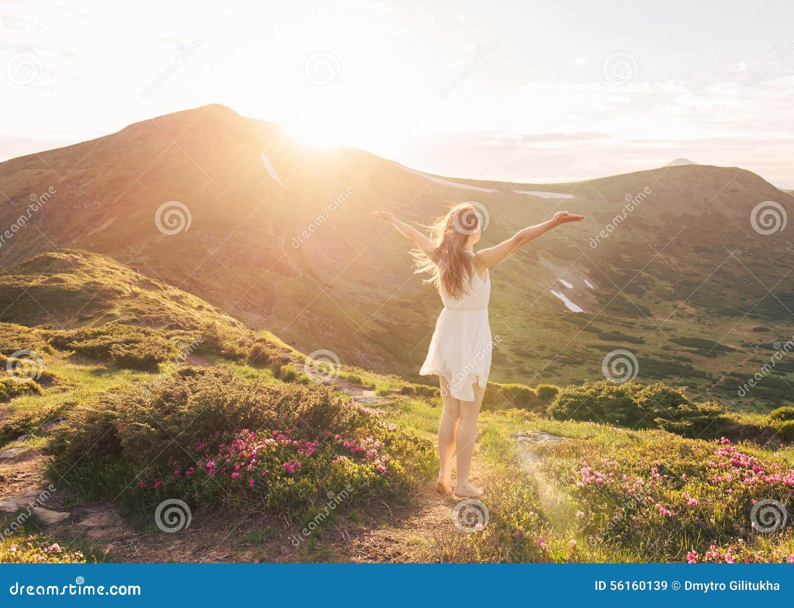 Mujer feliz que disfruta de la naturaleza en las montañas