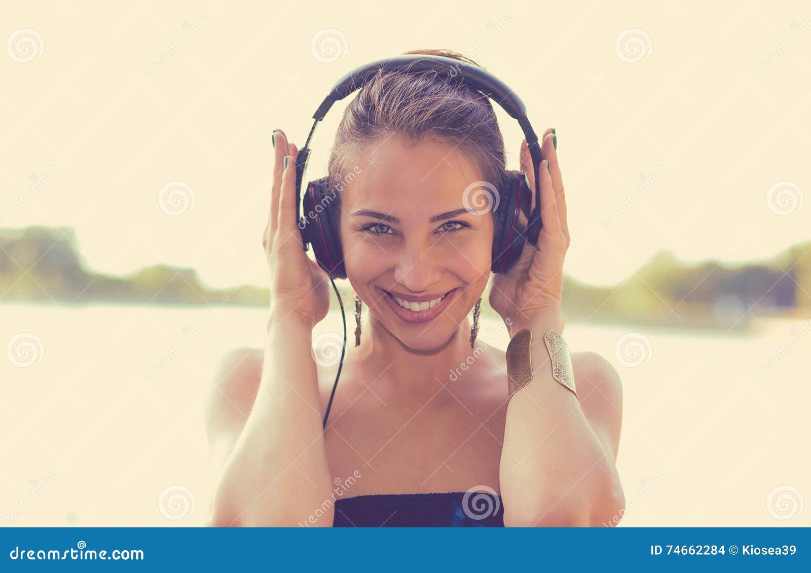 Mujer feliz que escucha la música en los auriculares al aire libre por el lago