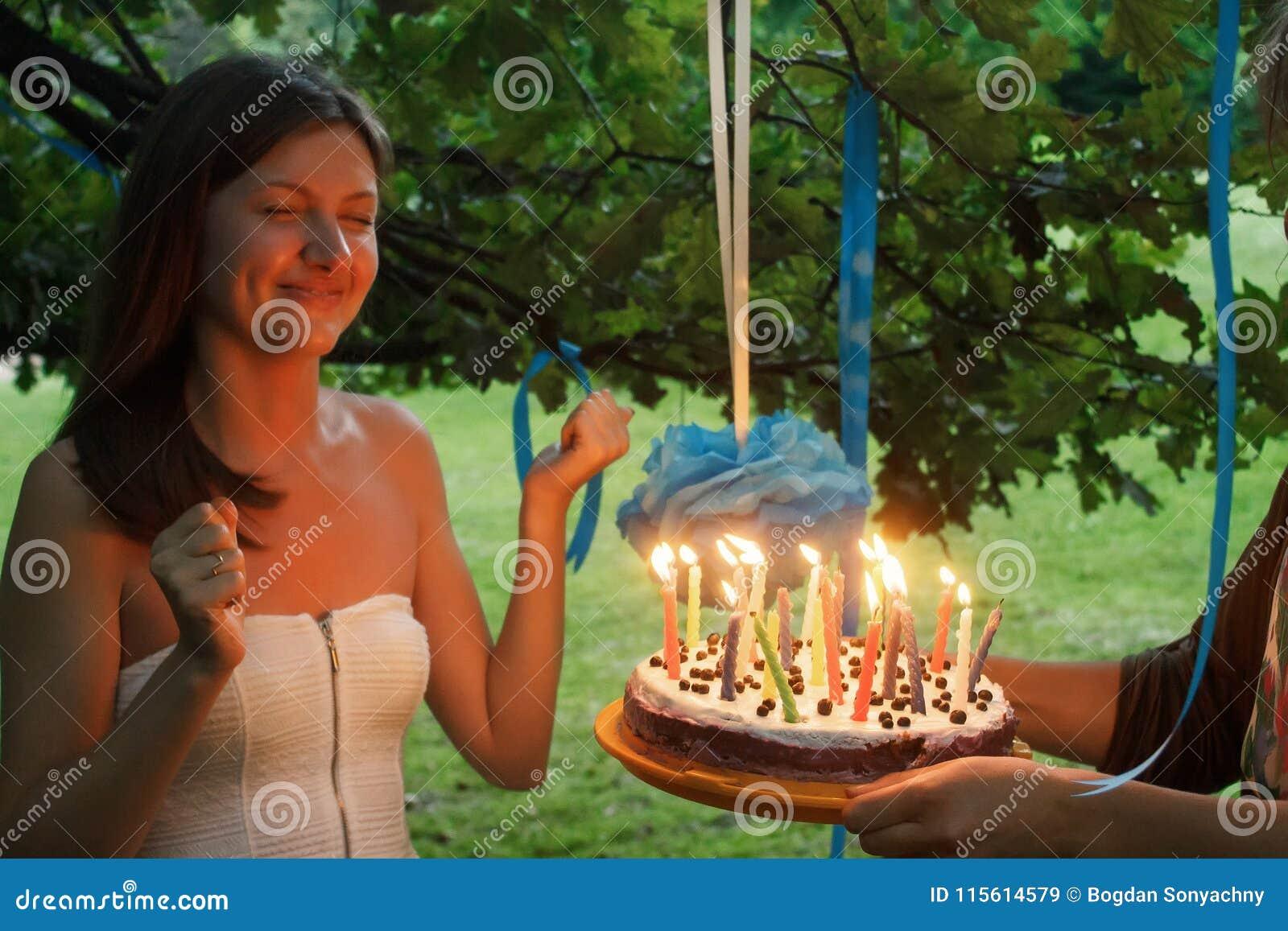 Mujer feliz que hace un deseo y que sopla velas en la torta en su bri