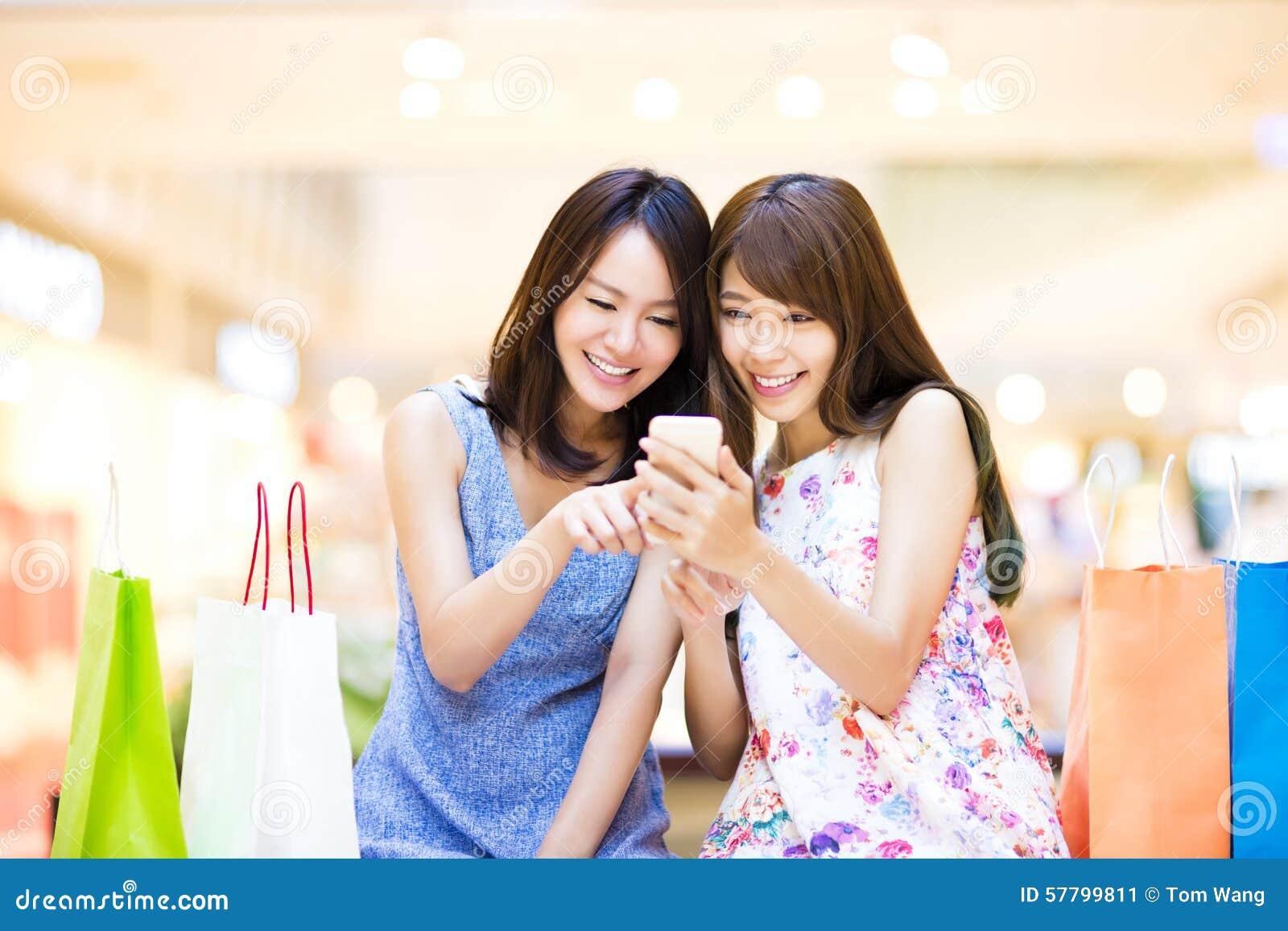 Mujer feliz que mira el teléfono elegante la alameda de compras