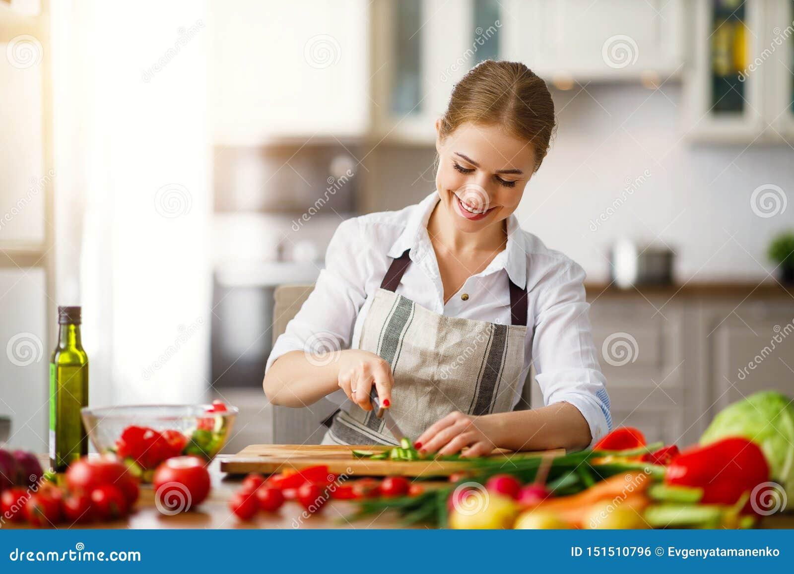 Mujer feliz que prepara la ensalada vegetal en cocina